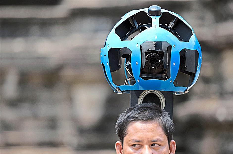 A Cambodian technician carries a back-pack mounted with a device housing 15 cameras as he demonstrates the technique used to digitally map the Angkor Wat temple, part of the Angkor architectural complex in north-western Cambodia on April 3, 2014. Cambodia's Angkor Wat has been digitally mapped for the first time, allowing people to visit the famed temples from the comfort of their armchair using Google Street View.  AFP PHOTO/Christophe ARCHAMBAULT