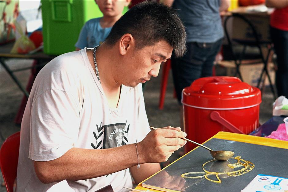 A candy artist showing off his skill at the carnival.