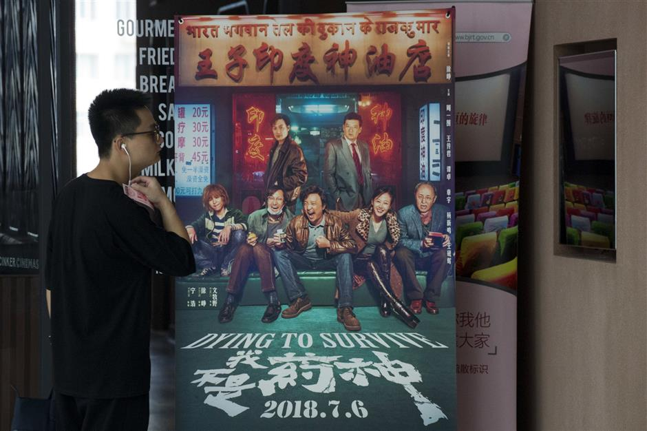 In this July 25, 2018, photo, a visitor to a cinema stands near the movie poster for the dark comedy 'Dying to Survive' in Beijing, China. Diagnosed with leukemia four months ago, Su Lingmin, a 27-year-old native of the north China city of Harbin is helping give a human face to the struggle for more affordable cancer drugs in China. That cause has been bolstered by the popularity of the recent film, 'Dying to Survive,' which follows the darkly comedic capers of a Chinese businessman-turned-drug smuggler who saves lives by illegally importing a leukemia drug from India, where it costs several times less than in China. (AP Photo/Ng Han Guan)