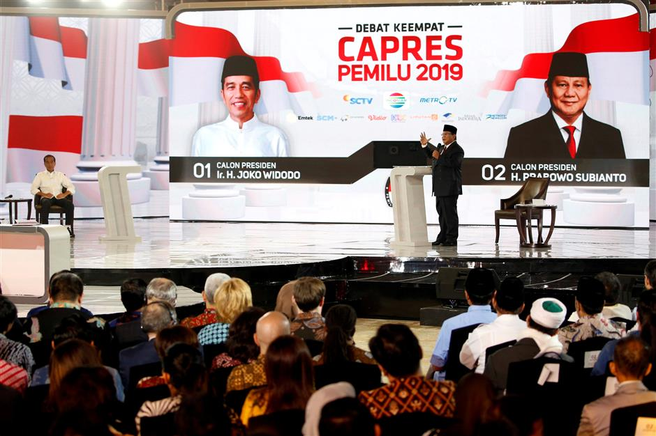 FILE PHOTO: Indonesia\'s presidential candidate Prabowo Subianto (R) speaks as his opponent Joko Widodo (L) listens during a televised debate ahead of the next general election in Jakarta, Indonesia, March 30, 2019. To match Insight  INDONESIA-ELECTION/FAKENEWS . REUTERS/Willy Kurniawan/File Photo