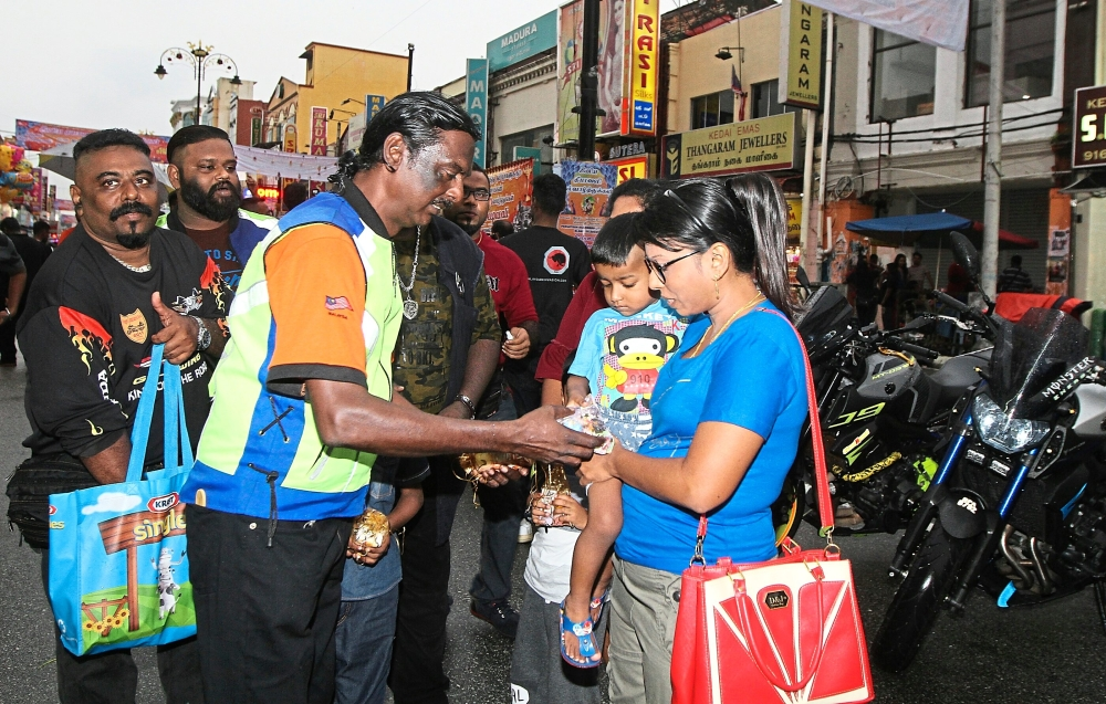 Mohan (left) presenting Deepavali cookies to a child in Jalan Tengku Kelana in  Klang.