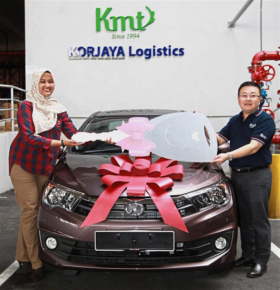 KMT Jaya Sdn Bhd Sales and Marketing strategic director Benny Lim Chee Keong handing over a mock car key to Nora at company's office in Shah Alam.