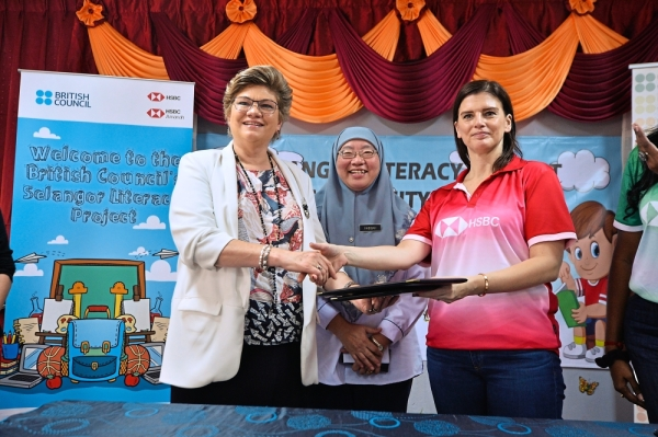 Deverall (left) and Latini shaking hands after the MoU signing ceremony while Dr Habibah (centre) looks on.