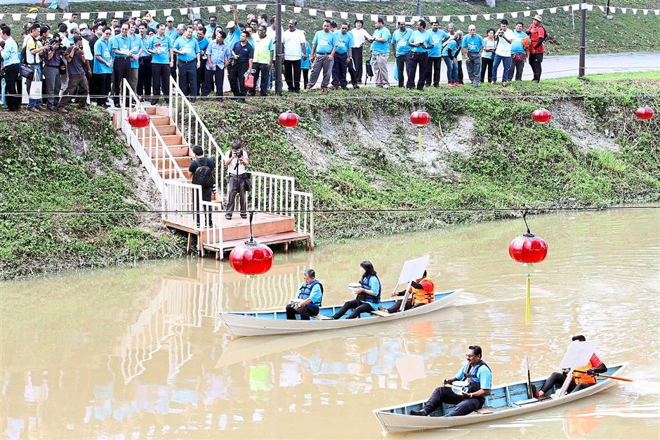 Representatives of the community around the three tributaries of Sungai Kinta - Sungai Senam, Sungai Kledang and Sungai Buntong being ferried on boats to release freshwater fishes into Sungai Kinta during the River Carnival.