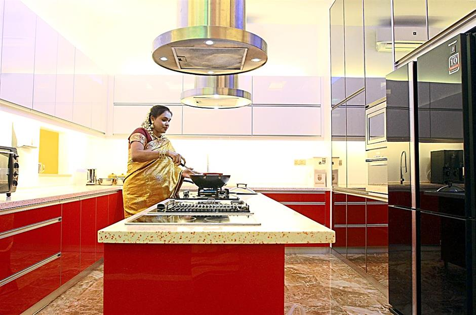 Thinarachagi preparing a meal at her kitchen which is located in the south-east, as recommended in Vasthu Sastra.