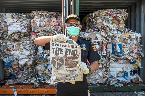 Too much trash: An Indonesian customs officer holding up a newspaper from a container of rubbish from Australia at a port in Surabaya. u2014 AFP