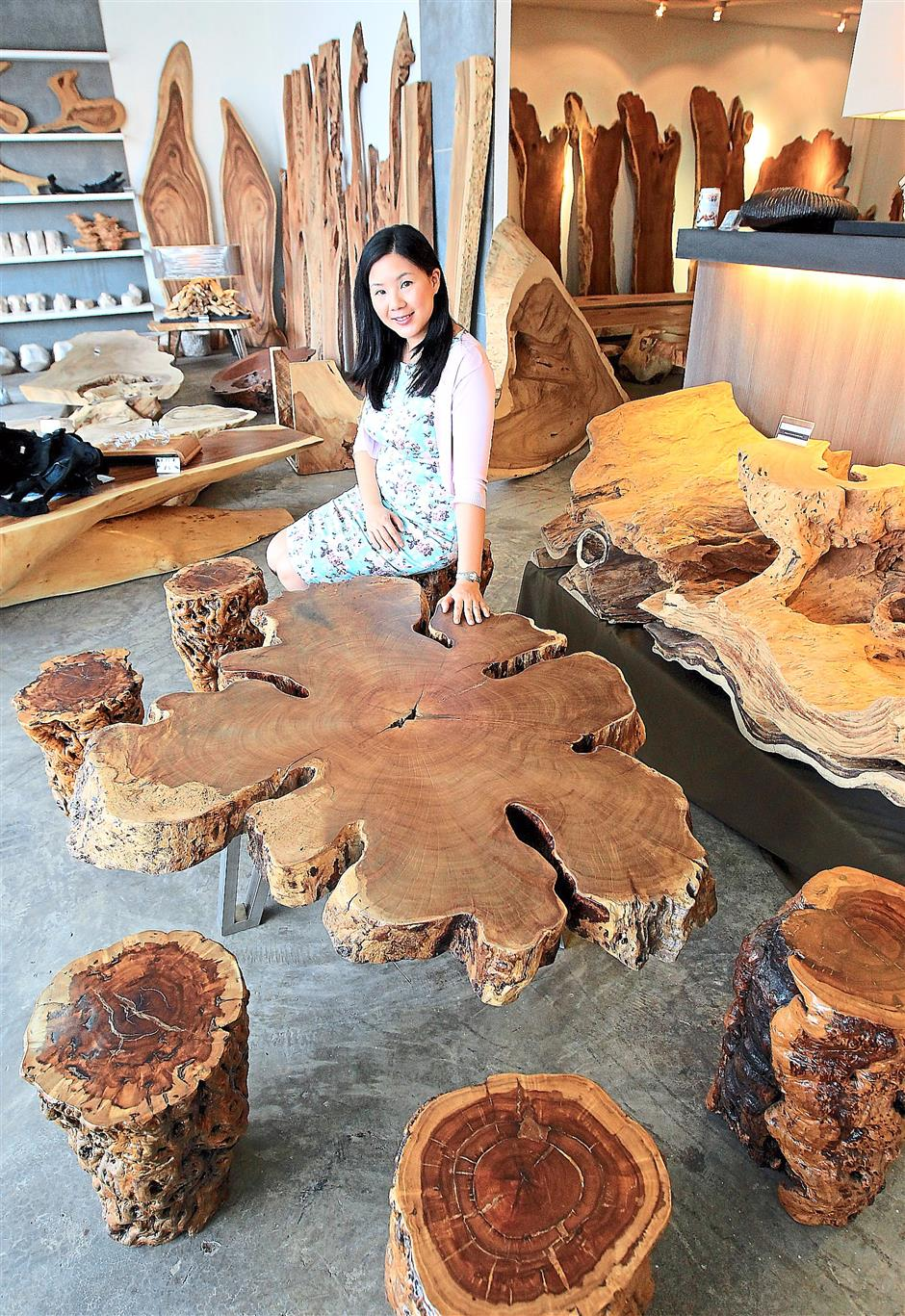 Nature in the home: Joey Woo, business partner and wife of Art of Tree founder Jeffrey Yang, with a floral-shaped coffee table. ?– Photos by IBRAHIM MOHTAR/The Star