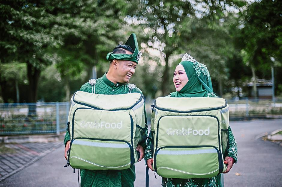 Afandi, 32, and Atiqah, 30, met while working as Grab Riders, giving their wedding photographer the idea to use the story as the theme of their photoshoot. — Amar Arif/The Hayat Co