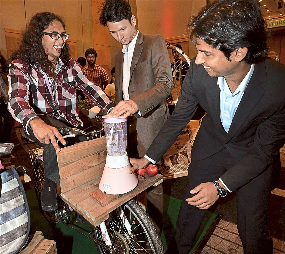 From left.... Biji Biji Initiative co-founder Gurpreet Singh Dhillon, Azam Hisham and Rashvin Pal Sing looking at a bicycle that is used to work a blender seen here during the Grants Awards Presentation.