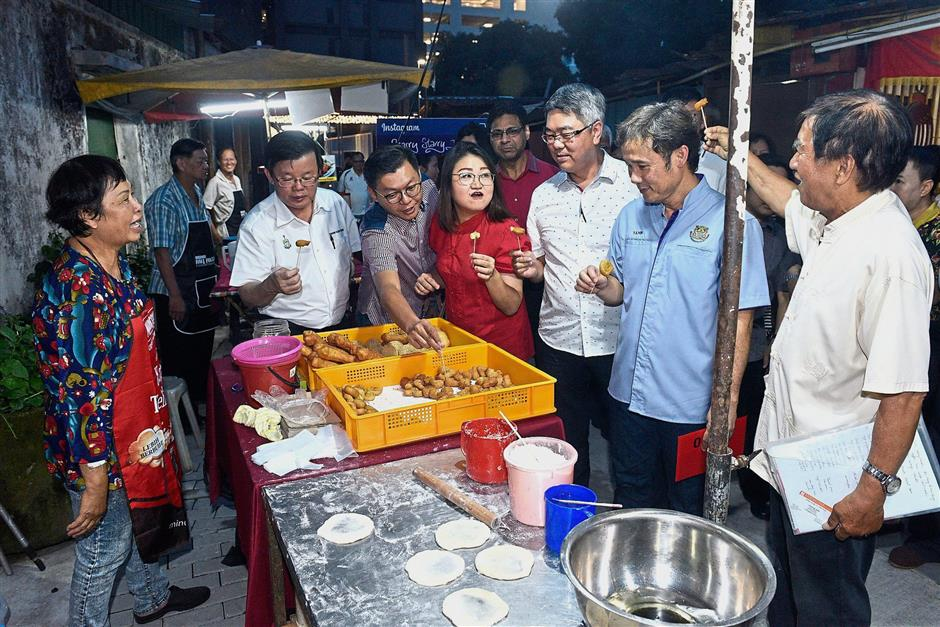 (From second left) Chow, Teh, Lim, Moh and Yew sampling snacks at one of the stalls along the stretch at the Starry Starry NiteMagazine Circus.