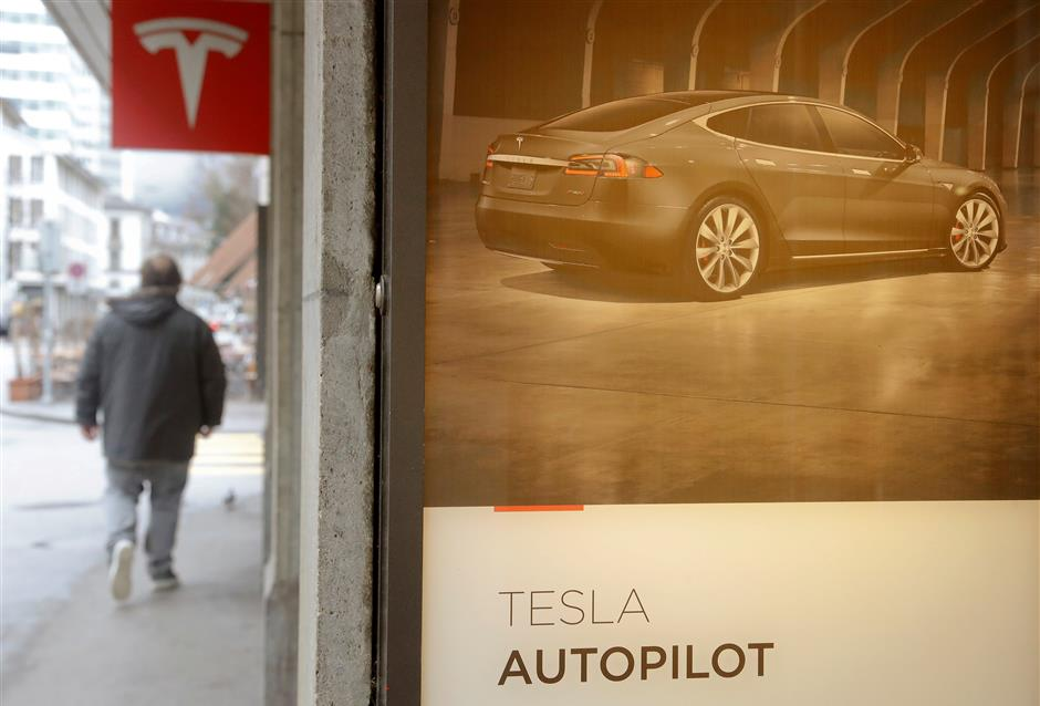 An advertisement promotes Tesla Autopilot at a showroom of U.S. car manufacturer Tesla in Zurich, Switzerland March 28, 2018. REUTERS/Arnd Wiegmann