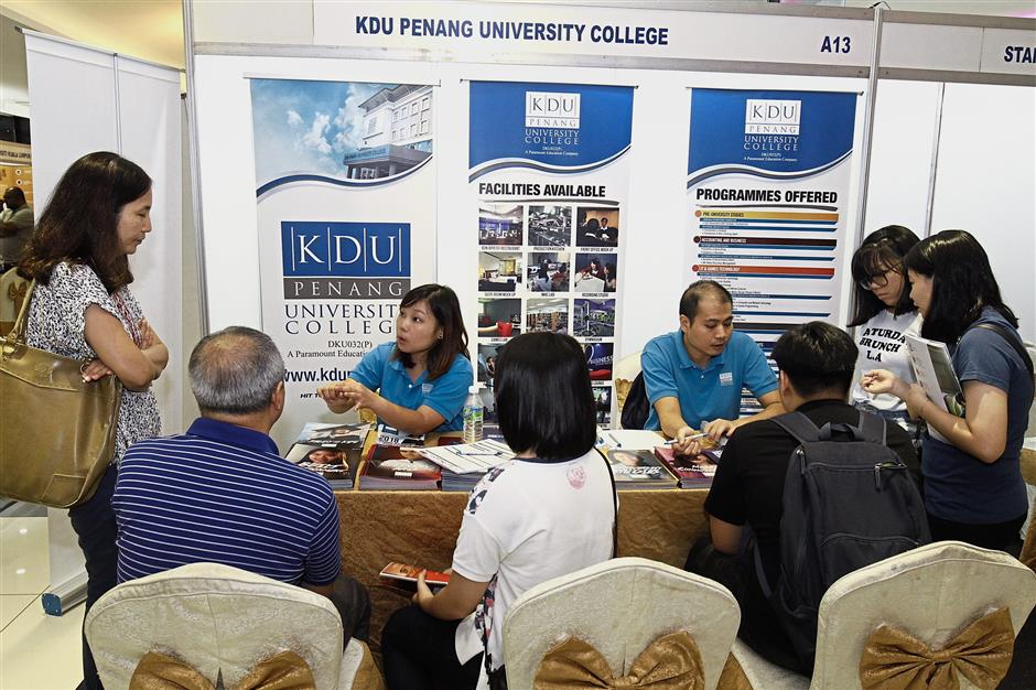 KDU Penang University College staff busy attending to visitors at their booth.