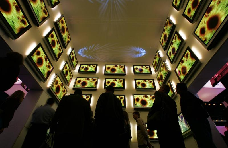 Attendees look up at a display of Panasonic plasma televisions at the 2005 International Consumer Electronics Show (CES) in Las Vegas. US economic growth likely slowed a bit in the third quarter as consumers kept a lid on spending - Reuters Photo.