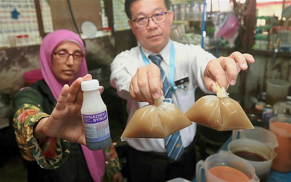 Ong (right) and Northeast district health officer Dr Umarazina Abdul Kadir showing the ketum and cough syrup found at a beverage stall during the raid.