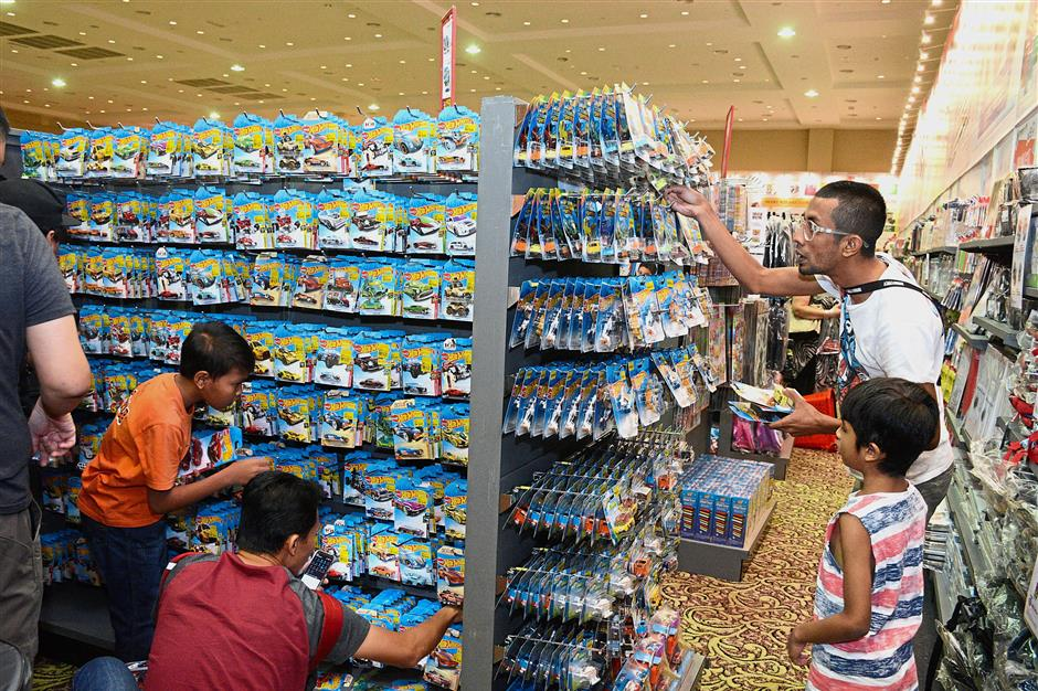 Abdul Hafeez (right, white T-shirt) and fellow Hot Wheels car collectors hunting for their desired models.