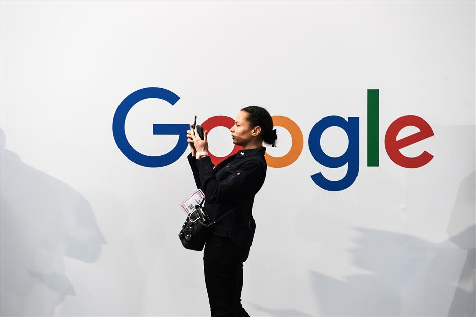 (FILES) In this file photo taken on May 16, 2019 a woman takes a picture with two smartphones in front of the logo of the US multinational technology and Internet-related services company Google as he visits the Vivatech startups and innovation fair, in Paris. - Google parent Alphabet\'s stock price leapt July 25, 2019, after reporting stronger-than-expected results in a quarterly update coming amid growing scrutiny of technology firms by antitrust regulators. (Photo by ALAIN JOCARD / AFP)