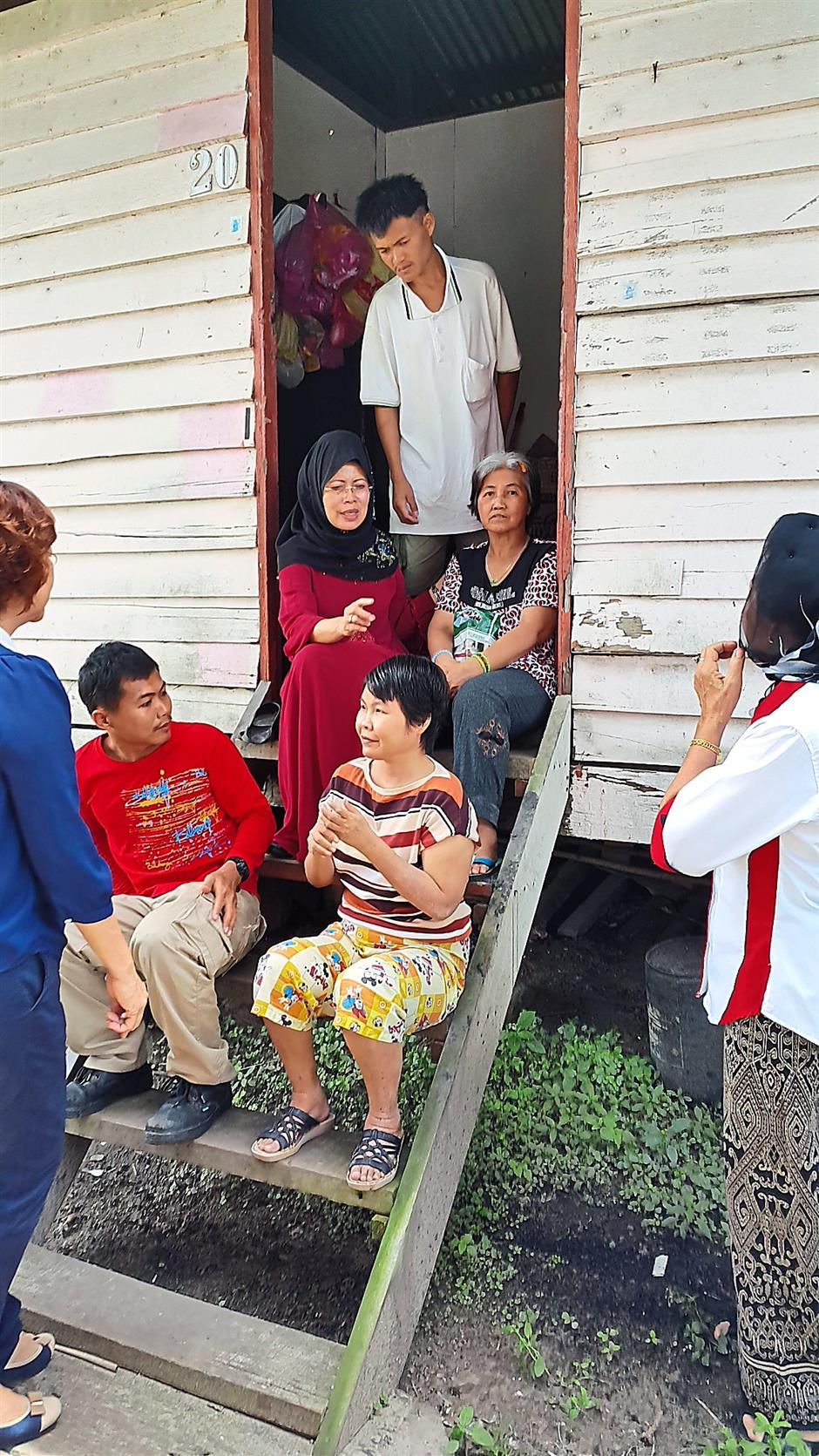 Sarawak Minister for women, family development and welfare Datuk Fatimah Abdullah visiting a family with mentally handicap children and land problem yesterday. Stephen pic