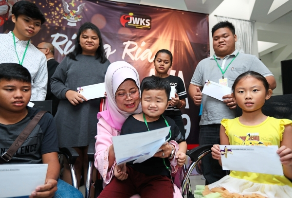 Fatimah (centre, in headscarf) with the citizenship recipients in Kuching. u2014 ZULAZHAR SHEBLEE/The Star