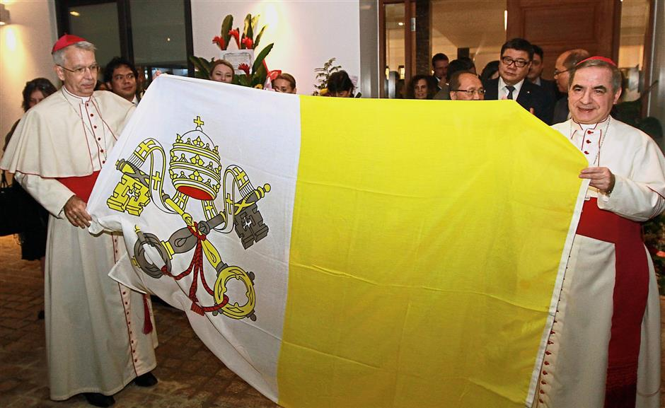 Archbishop Marino (left) and Archbishop Becciu holding up the flag of the Holy See.