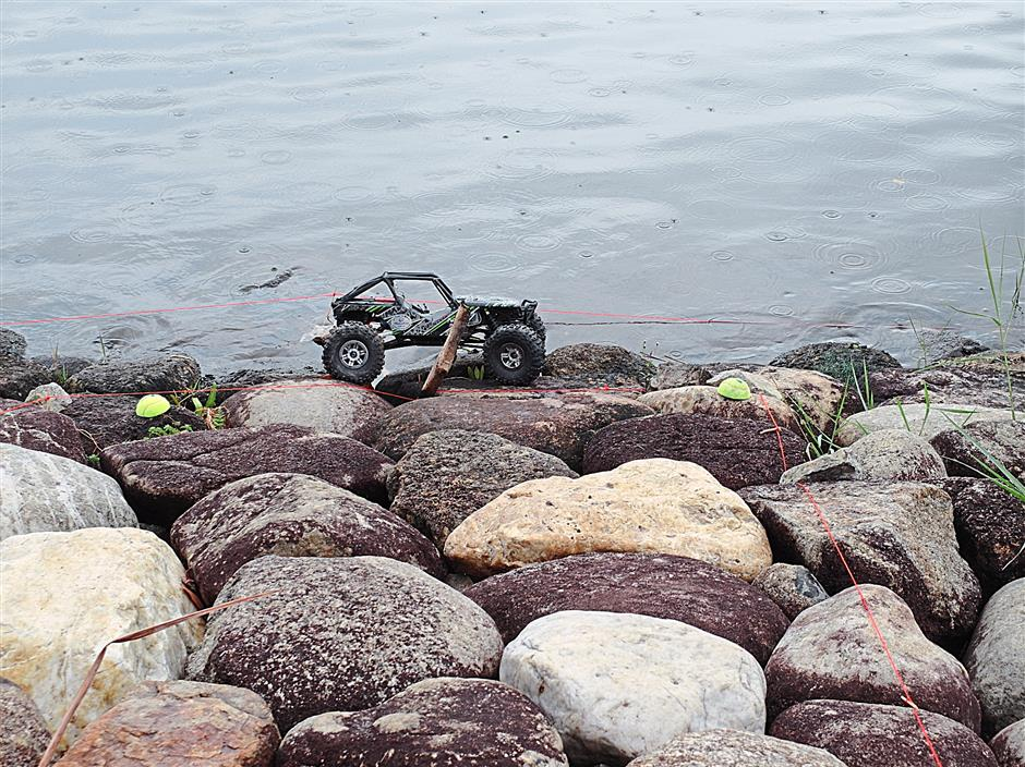 An RC crawler making its way on rocky terrain.The participants competing in the drifting category.Fong (right) using remote control to move an excavator which he constructed himself in the RC Truck and Construction Equipment category.A miniature truck station and excavation site, complete with gas station and elevated 'highway', is set up for the RC Truck and Construction category. Air RC enthusiast Wan Aziz (centre) posing with his team members Mat Sidi (right) and Nas Hazreeq at the event.Aza is active in local and international RC drifting competitions and says it's a fun and challenging hobby. Professional RC buggy racer and hobby shop owner Abdul Rahman says he travelled all the way from Johor to Putrajaya to compete in the event.Colourful custom modified EP boats on display at the Putrajaya RC Event 2014.