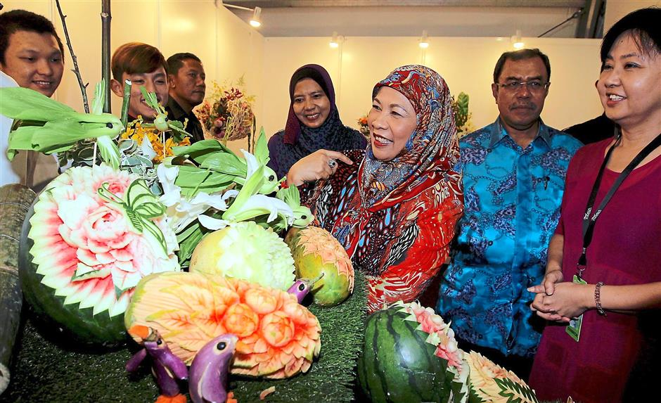 1 Tuanku Haminah (third from right) checking out the carved fruits at a booth at Floria. 2 A family taking the opportunity to cycle around the festival ground. 3 A visitor walking past by the Malacca-themed garden. 4 A child immersed in the colourful Pinwheel Garden. 5 The festival ground has a variety of themed gardens. 6 The Hobbiton Garden is a star attraction at Royal Floria Putrajaya 2015. Photos: RAJA FAISAL HISHAN