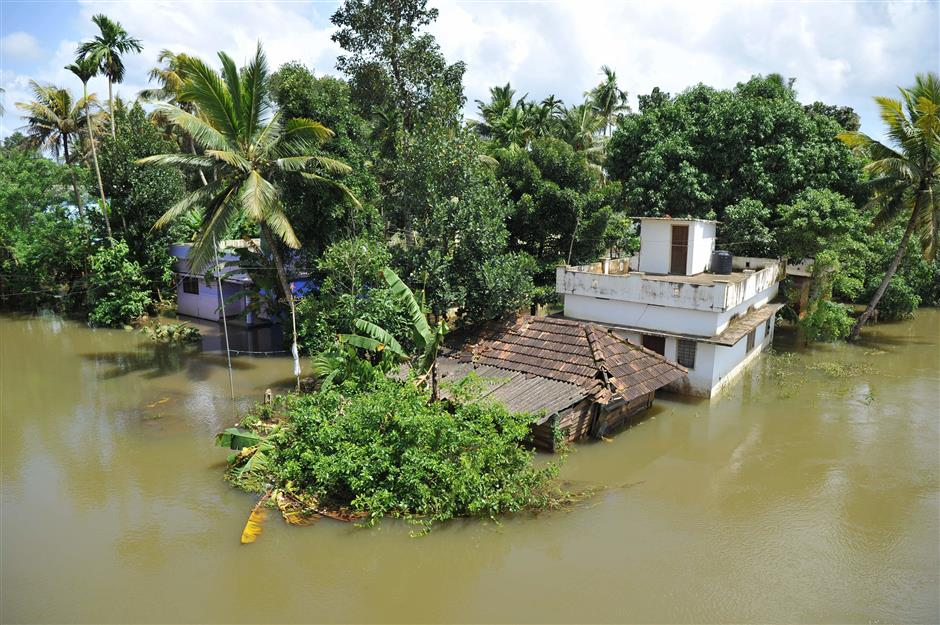 Marooned buildings on the banks of overflowing Pampa river are pictured in the flood waters in Alappuzha District in the south Indian state of Kerala, on August 21, 2018. - More than one million people have swarmed relief camps in India's Kerala state to escape devastating monsoon floods that have killed more than 410 people, officials said Tuesday as a huge international aid operation gathered pace. (Photo by MANJUNATH KIRAN / AFP)