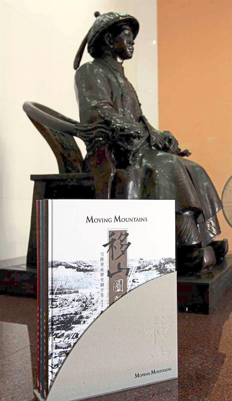 A massive project: 'Moving Mountains: A Pictorial History' of the Chinese in Selangor and KL involves four years of extensive research but the collection of photographs started about 20 years ago. In the background is a statue of one of Kuala Lumpur's founding fathers, Yap Ah Loy.