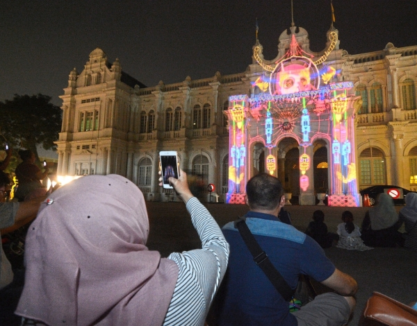 A spectator snapping away at a colourful image projected on the City Hall building.