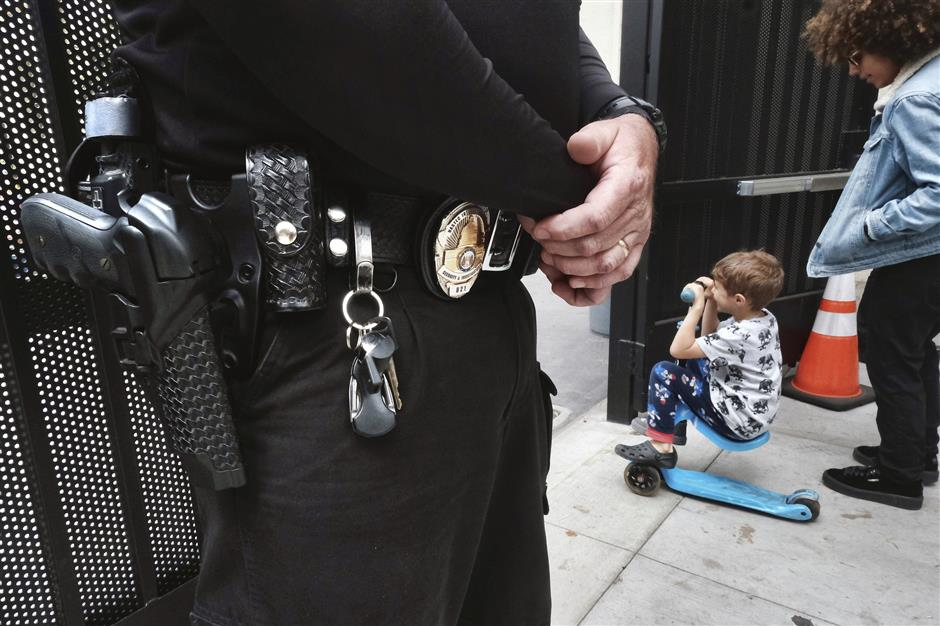 In this Monday May 13, 2019 photo, a security guard stands on watch at Beverly Hills Unified School District's K-8 Horace Mann School as students prepare to leave school for the day in Beverly Hills, Calif. Schools in Beverly Hills and others nationwide are adopting a strategy that aims to speed up the law enforcement response to shootings. Beverly Hills officials have added armed security guards, surveillance cameras and an app to report attacks and connect with police. (AP Photo/Richard Vogel)