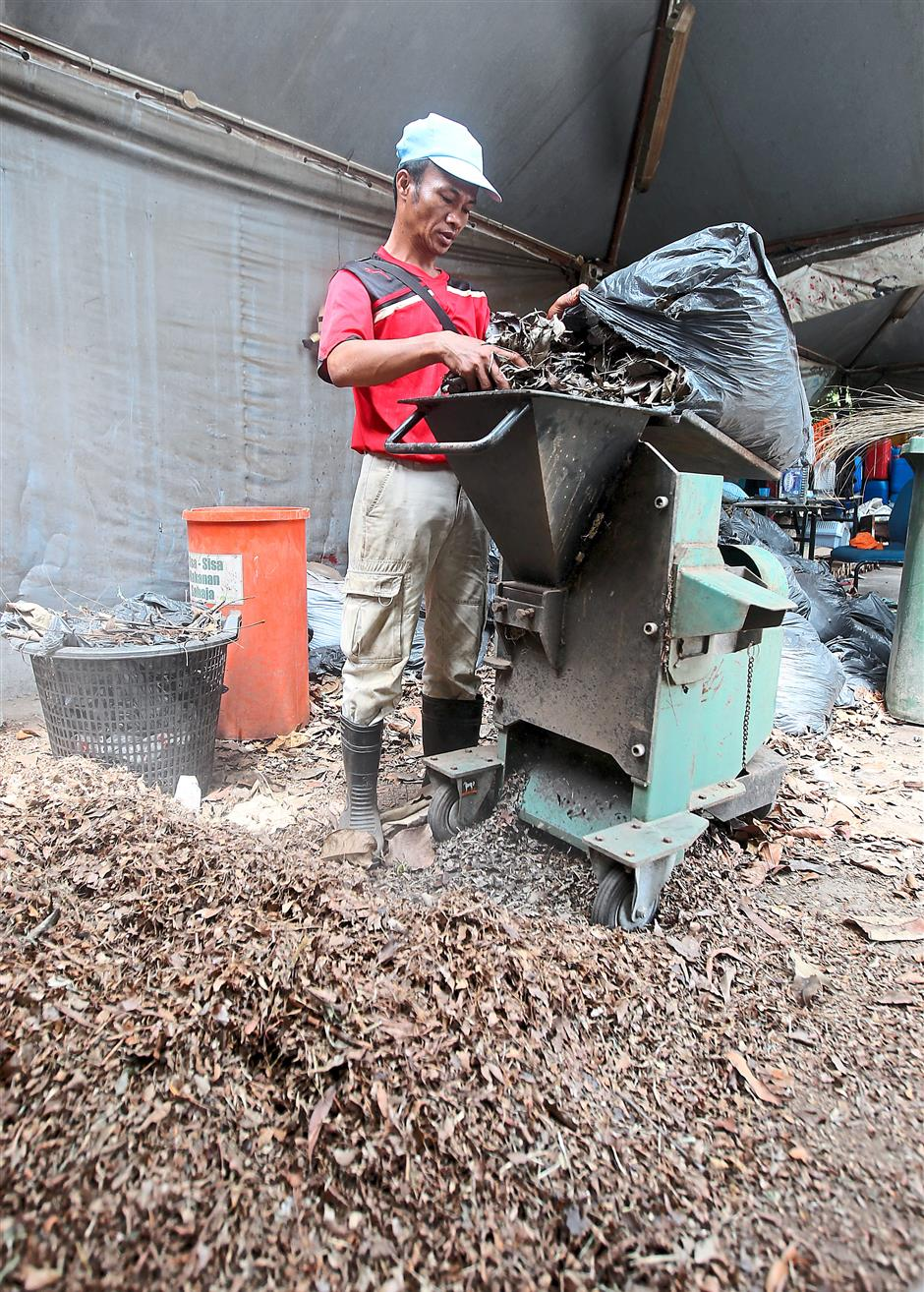 Minimising trash: Garden waste is shredded before being composted together with food waste under Universiti Malaya's Zero Waste Campaign. Photos: AZHAR MAHFOF/The Star