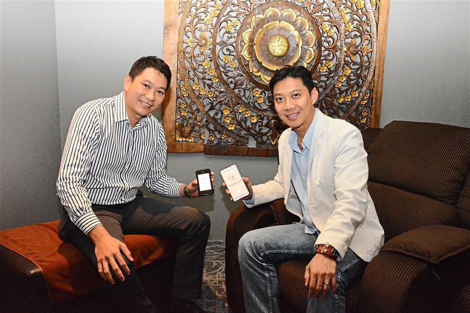 (From left) Danny Chan, business development director at ATA Retail Solution Sdn Bhd, and Patrick Wee displaying Healthland's newly launched mobile app which offers location-based services.