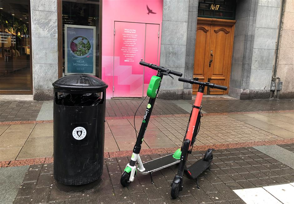 Electric scooters from Swedish startup VOI and U.S. rival Lime sit parked in the business district in Stockholm, Sweden July 6, 2019. Picture taken July 6, 2019. REUTERS/Esha Vaish