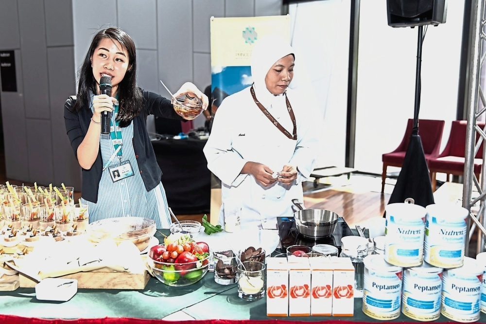Asiah (right) preparing dark chocolate pudding with chocolate ganache while Ng spoke about the nutritional value found in the recipes launched by Nestlu00e9 Health Science and Prince Court Medical Centre.