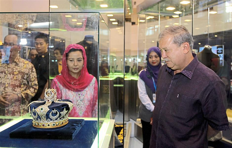 Crown of glory: Johor Ruler Sultan Ibrahim I and Permaisuri Johor Raja Zarith Sofiah looking at the royal crown worn during the coronation.