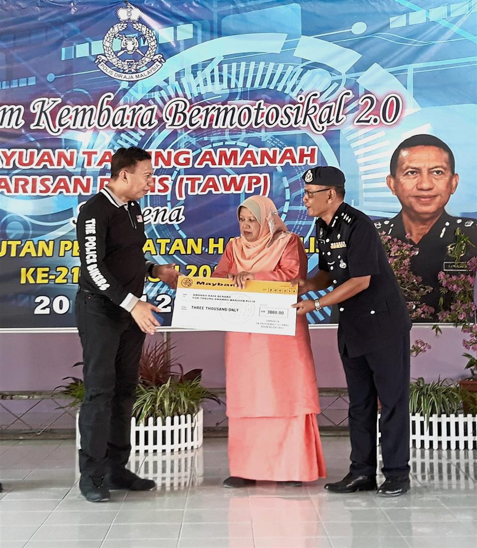 Zaiton (centre) witnessing the handing over of a mock cheque between ACP Zaharudin (right) and Comm Zulkifli during the convoy's stopover in Sungai Besar.