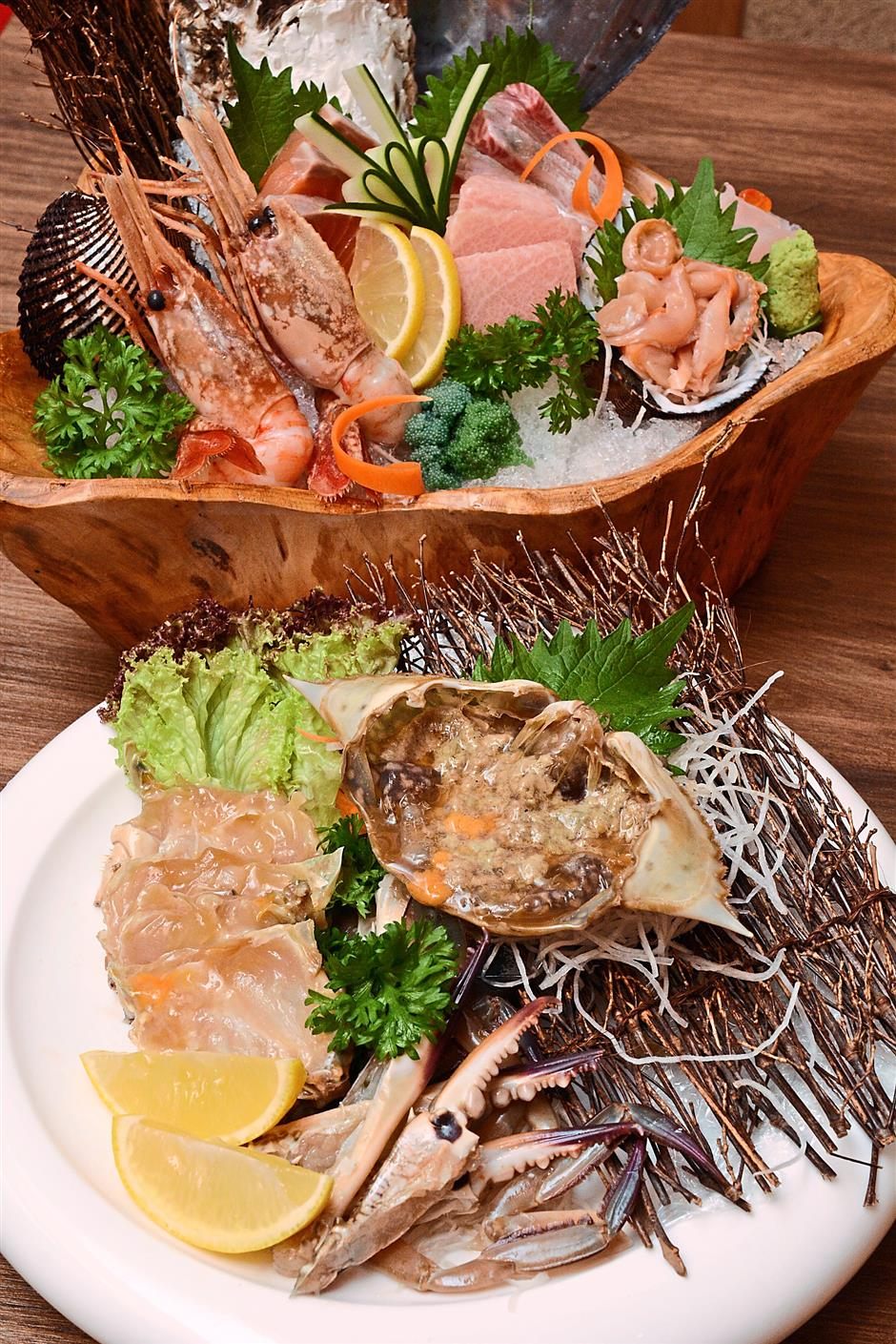 3 The Marinated Flower Crab (bottom) and Assorted Seasonal Sashimi Platter (top) are ideal for seafood lovers yearning for a fresh taste of the sea.