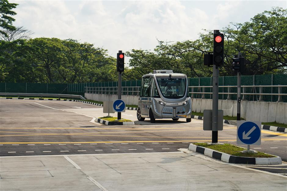 A Navya SAS autonomous electric passenger bus waits at a signal light while travelling along the test circuit at the Centre of Excellence for Testing & Research of Autonomous Vehicles (CETRAN) of Nanyang Technology University in Singapore, on Tuesday, May 22, 2018. In the race to deploy driverless public transport, Singapore has built a mini town that could vault it into pole position. The 2-hectare complex, unveiled in November, has intersections, traffic lights, bus stops and pedestrian crossings, all built to the specifications that Singapore uses for its public roads. Photographer: Nicky Loh/Bloomberg
