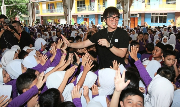 Centre of attention: Jinnyboy giving high fives to pupils during a #StandTogether National Kindness Week school visit.