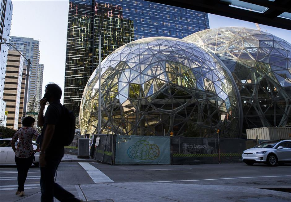 Pedestrians walk past the Amazon Spheres on Thursday, August 17, 2017 in downtown.  (Kjell Redal/Seattle Times/TNS)  OUTS: SEATTLE OUT, USA TODAY OUT, MAGAZINES OUT, ONLINE OUT, TELEVISION OUT, SALES OUT.