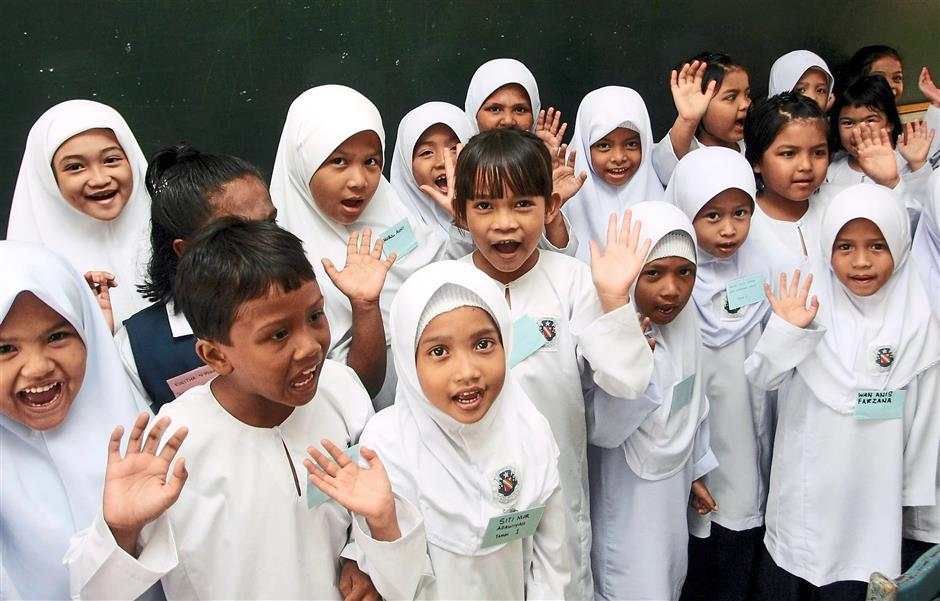 In good spirits:  Year One pupils of SK Convent in Alor Setar waving during their first day of school.