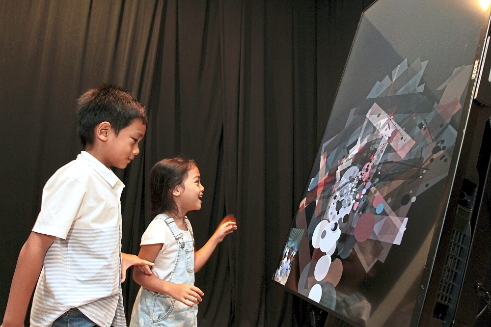 Muhammad Raihan Haris Abadi, 6 (left), and his sister, Nur Almas, having fun with Syafiq Abdul Samat's interactive piece called 'Noise Painter' that responds to light and noise.