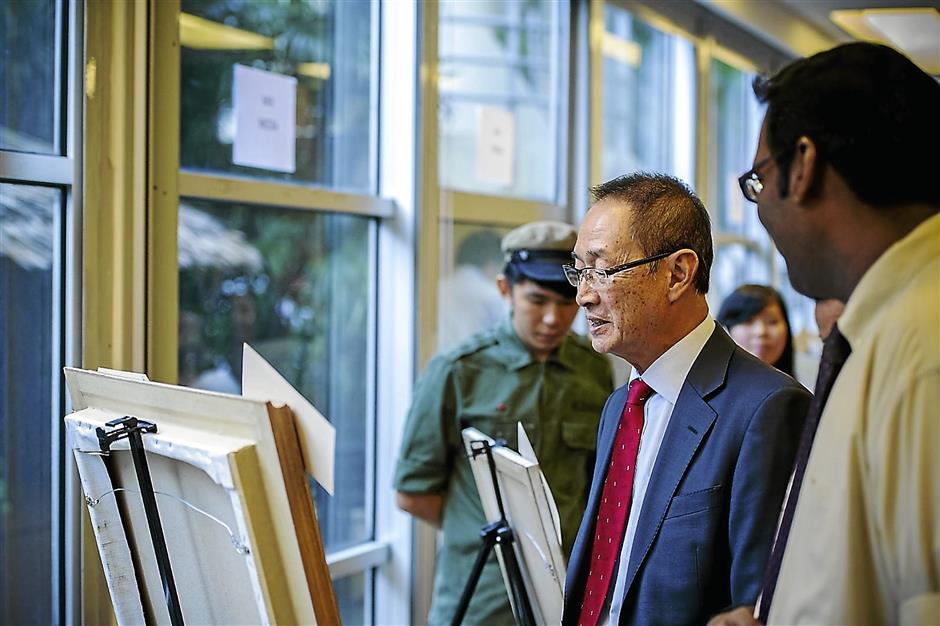 Datuk Robert Cheim, Chairman, Tanjong plc (centre) viewing a winning artwork
