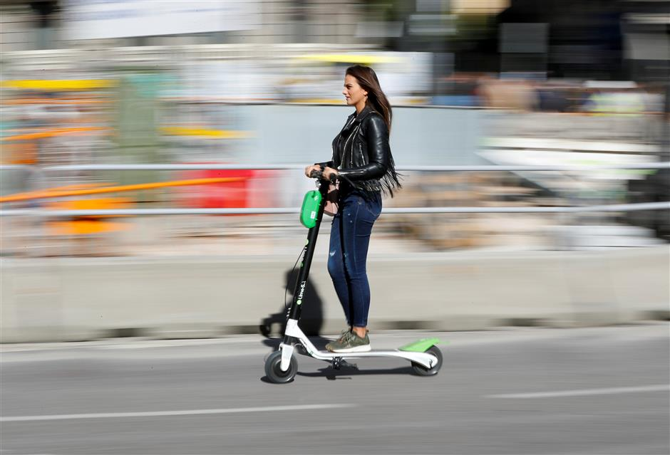 A woman rides a dock-free electric scooter Lime-S by California-based bicycle and scooter sharing service Lime, on a street in Madrid, Spain, October 24, 2018. REUTERS/Paul Hanna