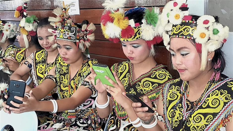 Orang Ulu ladies in traditional customes playing with their handphones while enjoying the Gawai Dayak festival in Sungai Asap in northern Sarawak. Stephen pic
