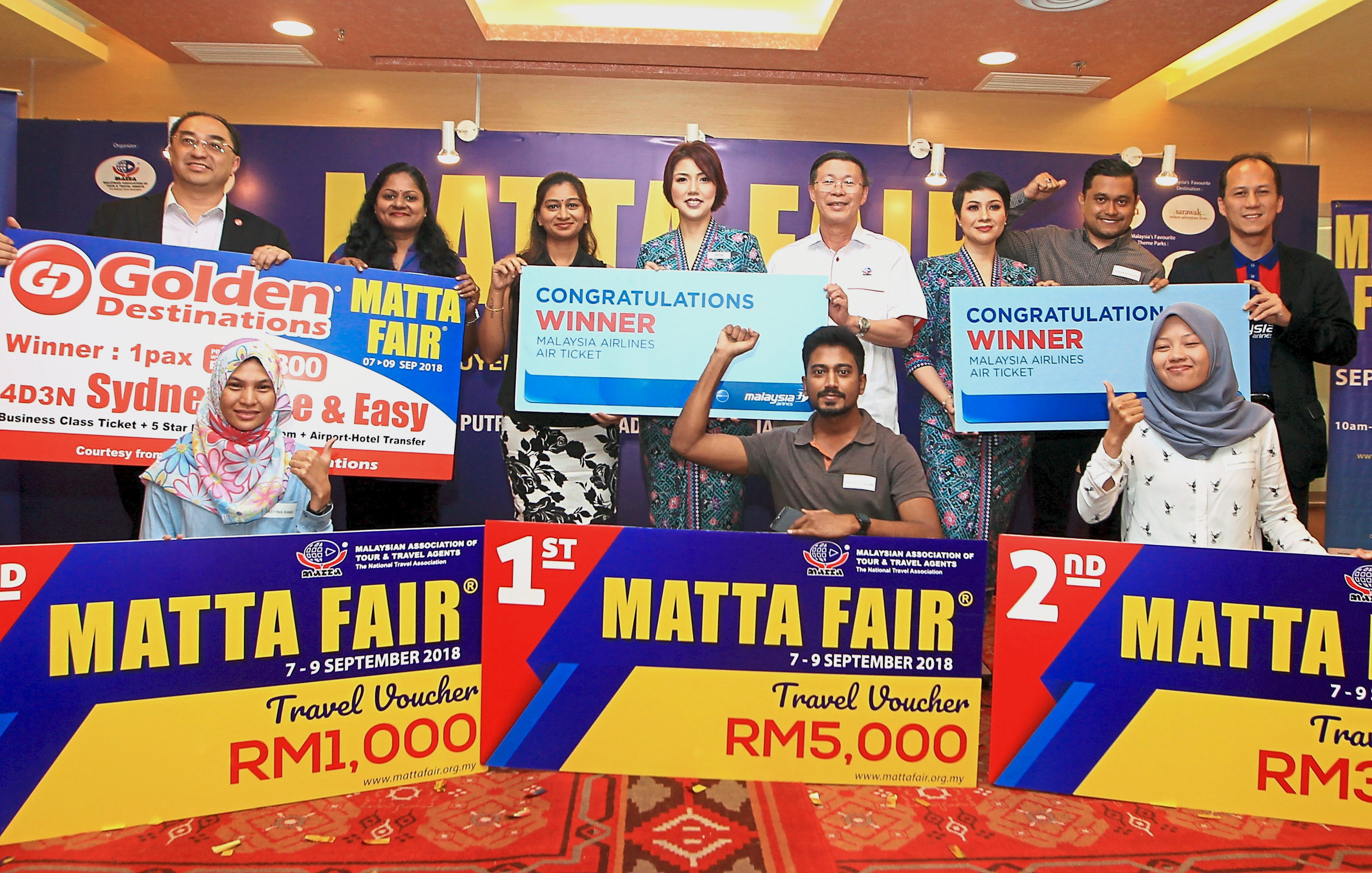 Golden Destinations  managing director Mita Lim (back row, left), Tan (fifth left) and Malaysia Airlines senior manager sales development Azrin Muzaffar (right) presenting the grand prizes to the lucky winners.