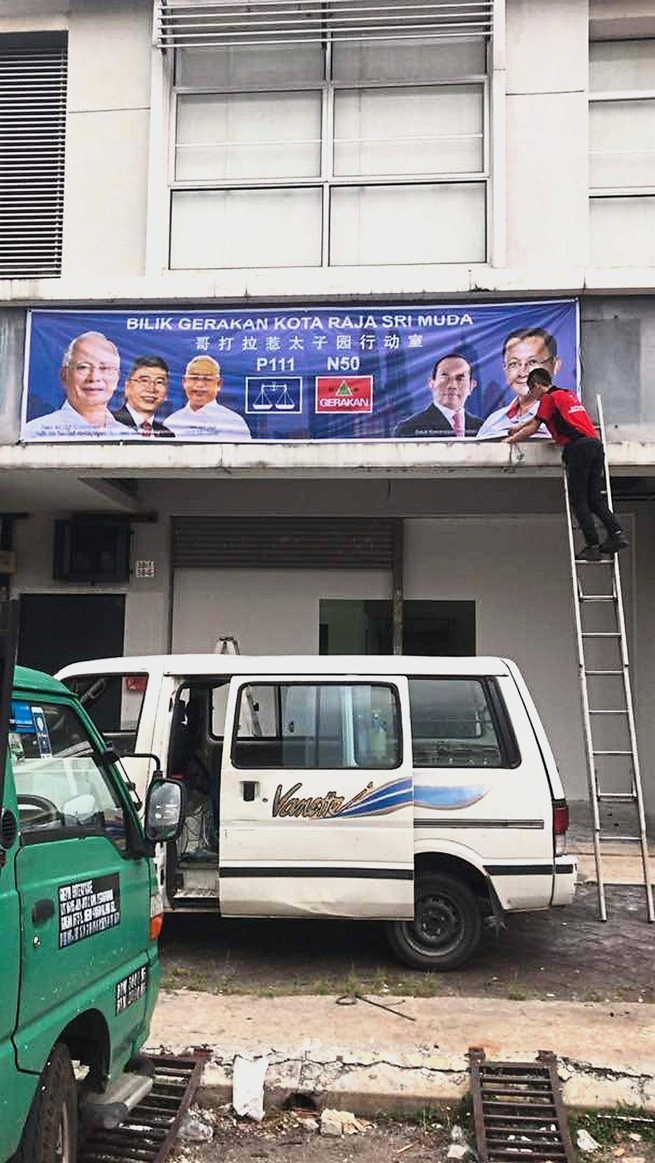 A party worker putting up a banner at the Gerakan operations centre to be launched today in Kota Kemuning.