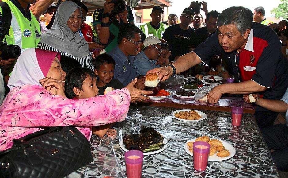 Here's one for you: Ahmad Zahid distributing bread to the flood victims at SK Sayong flood relief centre.
