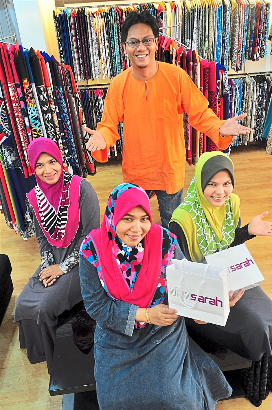 Fadil (in orange) started making his line of instant tudung in 2009.