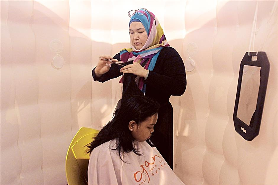 Hairstylist Nur Azmina Ahmad Burhan, 27, giving a little girl a haircut in the inflatable 'Pop Up Salon' located on the sidewalk along Jalan Tunku Abdul Rahman. FAIHAN GHANI/The Star.