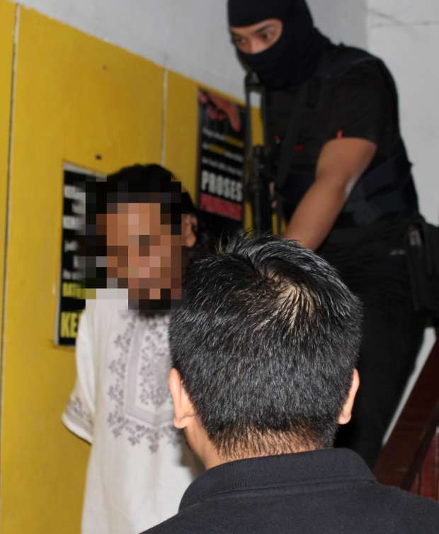 Game over: Bukit Aman Special Branch Counter Terrorism Division personnel apprehending the 30-year-old main suspect, believed to be a senior leader of the militant group in Sandakan, Sabah.